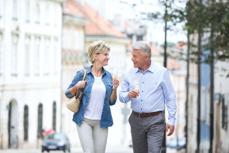 Pares de meia idade felizes que olham se ao guardar cones de gelado na cidade fotos de stock royalty free