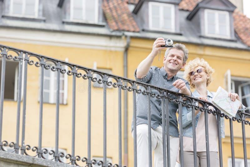 Pares de meia idade felizes que tomam o selfie através da câmara digital contra a construção foto de stock