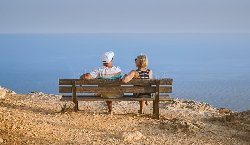 Pares de meia idade que sentam-se no banco e na apreciação da vista foto de stock