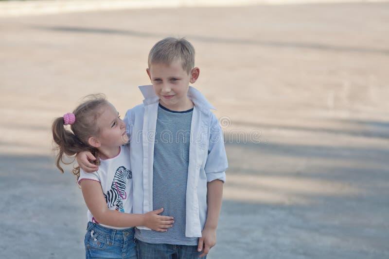 Pares de menino novo e de menina que andam junto na estrada foto de stock