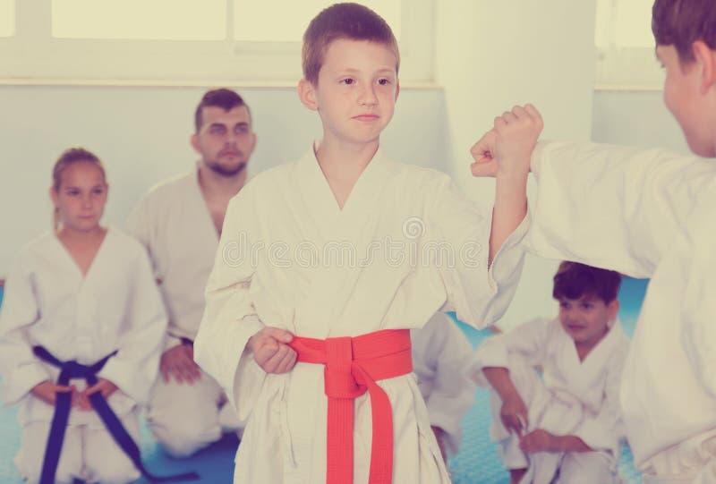 Pares de meninos que lutam no boxe de treino para usar movimentos novos fotografia de stock royalty free