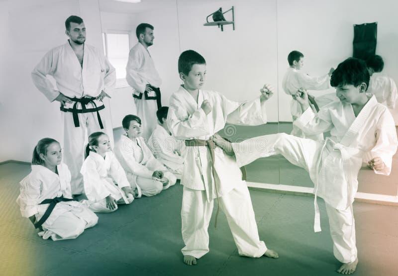 Pares de meninos que praticam movimentos novos do karaté foto de stock