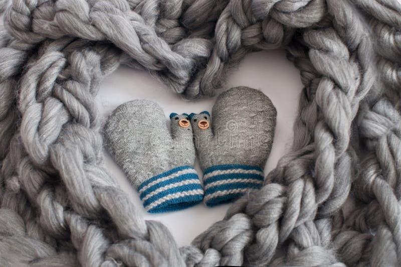 Pares de mitenes feitos malha cinzentos cercados pela tela de lã cinzenta em uma forma do coração imagens de stock