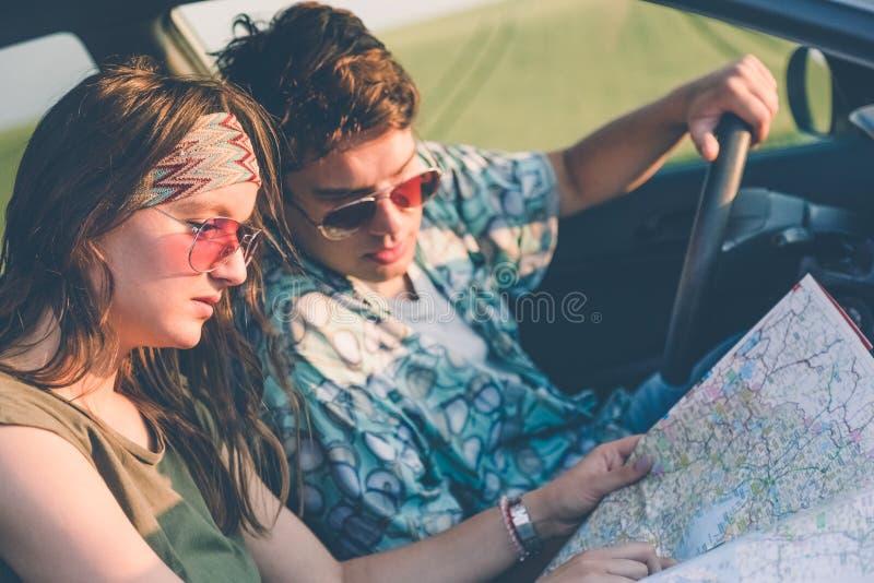 Pares de moda en interior del coche usando mapa en el roadtrip para las direcciones foto de archivo libre de regalías