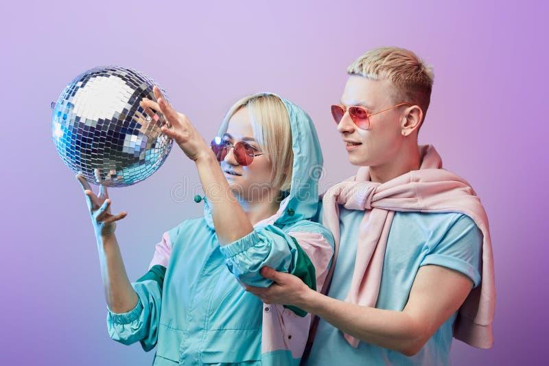 Pares de moda jovenes de los bailarines que presentan con la bola de discoteca en el fondo violeta imágenes de archivo libres de regalías