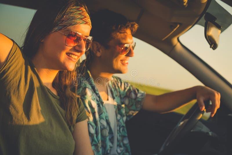 Pares de moda jovenes que conducen a lo largo de la carretera nacional en la puesta del sol imágenes de archivo libres de regalías