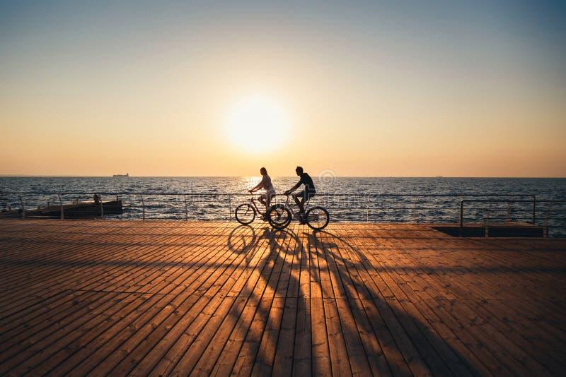 Pares de modernos novos que dão um ciclo junto na praia no céu do nascer do sol em horas de verão de madeira da plataforma fotos de stock royalty free