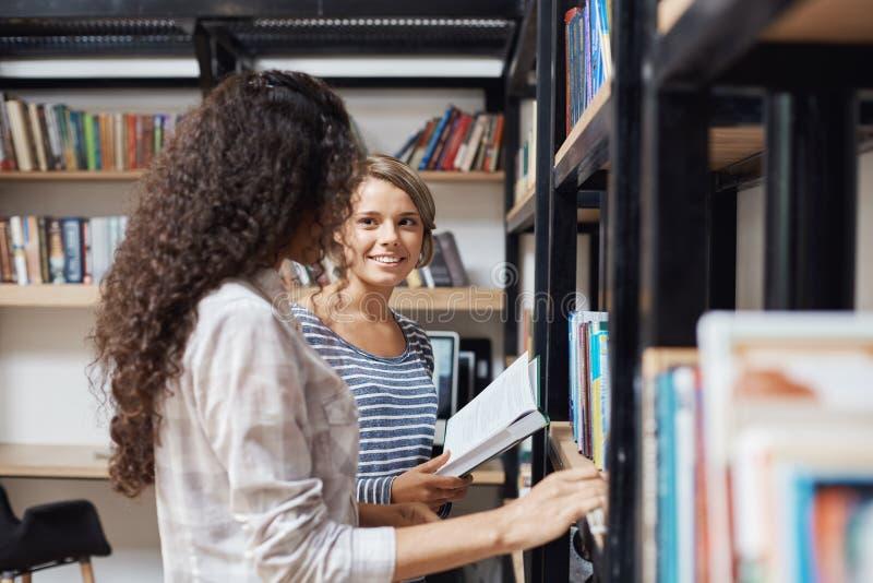 Pares de muchachas hermosas jovenes en la ropa elegante casual que coloca los estantes cercanos en biblioteca, mirando uno a fotos de archivo