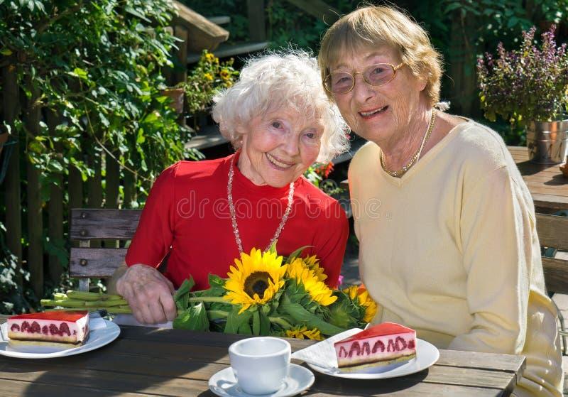 Pares de mujeres sonrientes que comen la empanada en café imagenes de archivo