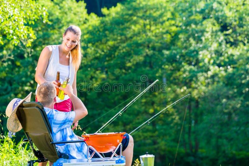 Pares de mulher e de homem que comem a cerveja quando pesca desportiva imagem de stock royalty free