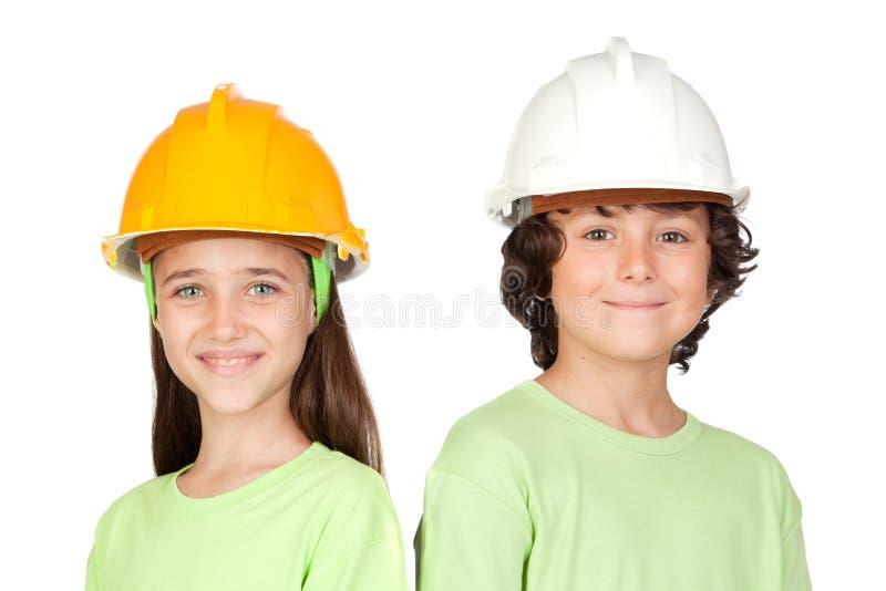 Pares de niños con el casco imagenes de archivo
