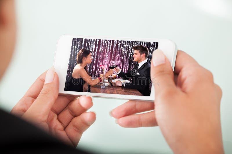 Pares de observação da mulher de negócios que brindam copos de vinho no telefone celular fotografia de stock royalty free