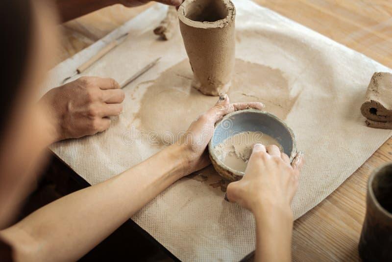 Pares de oleiro que fazem a substância da argila para formar o vaso foto de stock