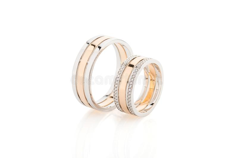 Pares de oro rosado y de anillos de bodas del oro blanco aislados en blanco foto de archivo libre de regalías