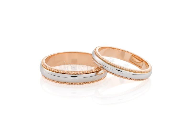 Pares de oro rosado y de anillos de bodas del oro blanco aislados en el fondo blanco imagenes de archivo