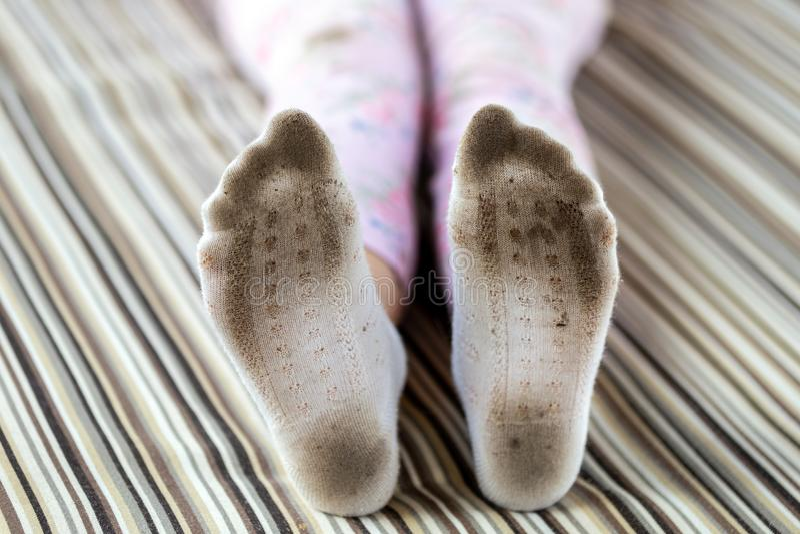 Pares de pés da criança em peúgas brancas manchadas sujas Peúgas sujadas criança ao jogar fora Descoramento da roupa das crianças fotos de stock royalty free