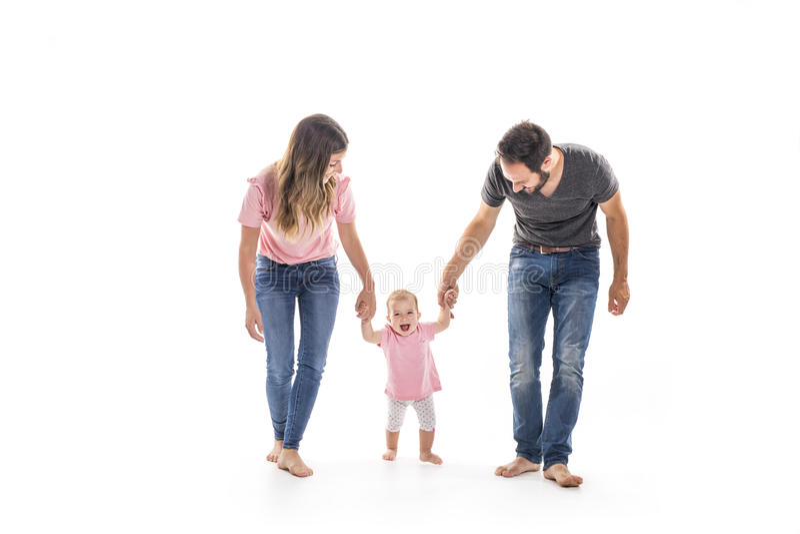 Pares de pais novos que ajudam seu bebê a fazer primeiras etapas no assoalho em sua casa fotos de stock