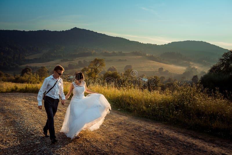 Pares de passeio do recém-casado ao longo da estrada durante o por do sol O noivo considerável está guardando a mão da noiva lind foto de stock