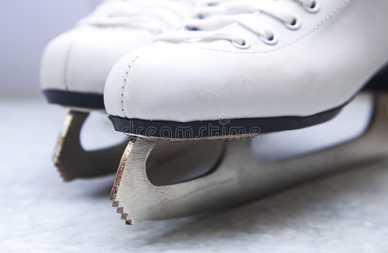 Pares de patins do branco da figura fêmea fotografia de stock royalty free
