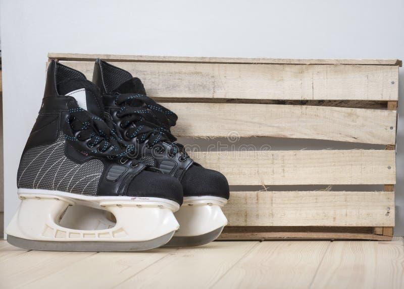 Pares de patins pretos do hóquei em um tabletop de madeira fotos de stock