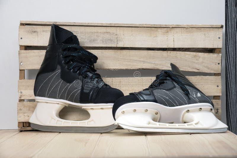 Pares de patins pretos do hóquei em um tabletop de madeira imagem de stock