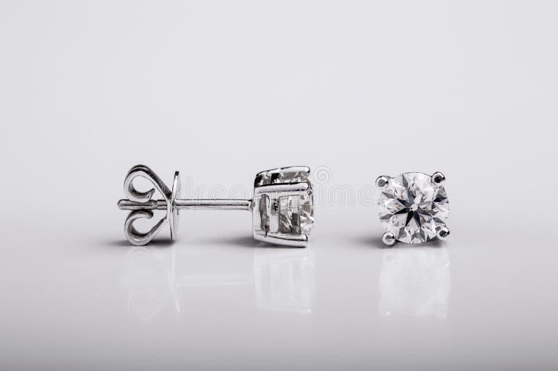 Pares de pendientes del perno prisionero del diamante y del oro blanco en el fondo blanco foto de archivo libre de regalías