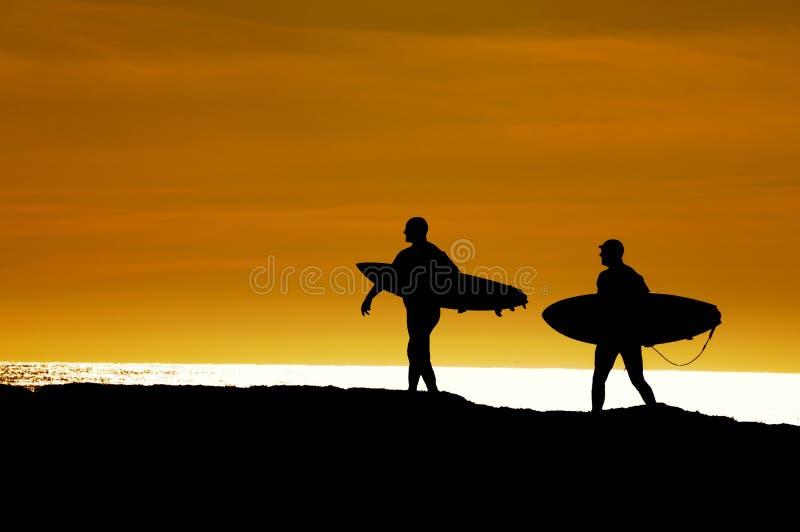 Pares de personas que practica surf que dirigen hacia fuera en la puesta del sol foto de archivo