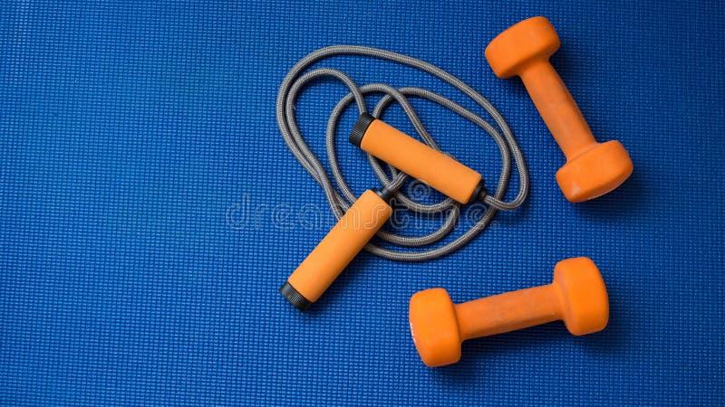 Pares de pesas de gimnasia anaranjadas y cuerda de salto en fondo azul de la estera de la yoga imagenes de archivo