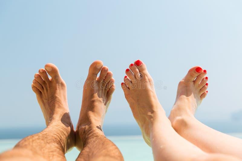 Pares de pies en la playa imagenes de archivo