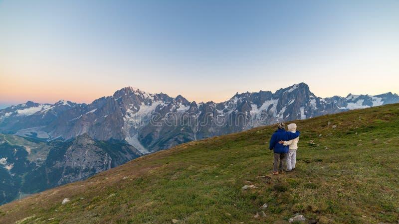 Pares de povos que olham o nascer do sol sobre o pico de montanha de Mont Blanc 4810 m ` Aosta de Valle d, aventuras italianas do fotos de stock