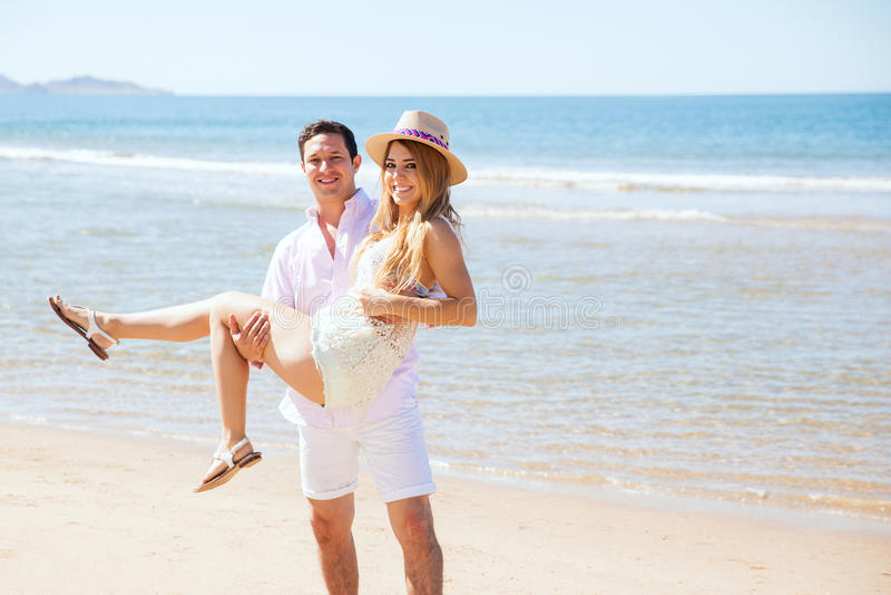 Pares de recienes casados en la playa fotografía de archivo