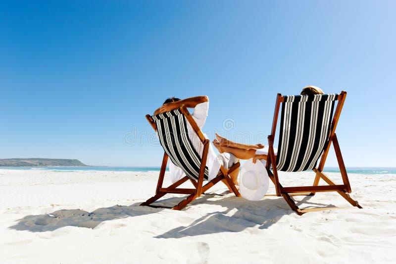 Pares de relaxamento da praia do verão fotografia de stock royalty free