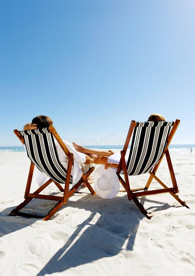 Pares de relaxamento da praia do verão foto de stock