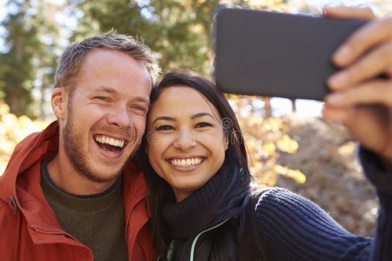 Pares de risa de la raza mixta que toman un selfie en un bosque fotos de archivo libres de regalías