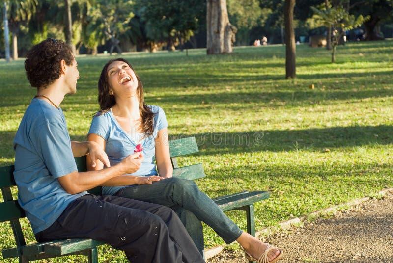 Pares de risa en un banco de parque - horizontal imagen de archivo libre de regalías