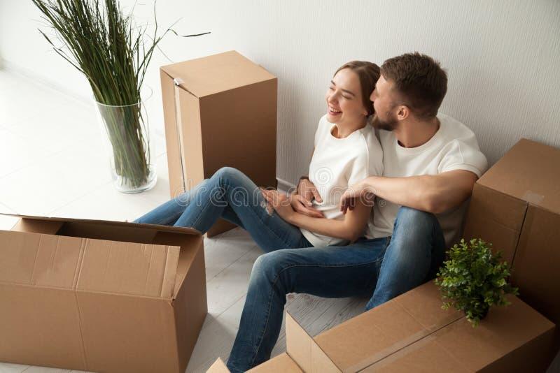 Pares de risa jovenes que se sientan en piso en el nuevo apartamento fotos de archivo libres de regalías