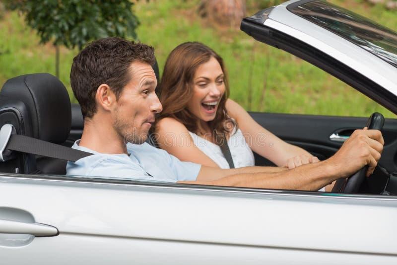 Pares de riso que conduzem em um convertible fotografia de stock