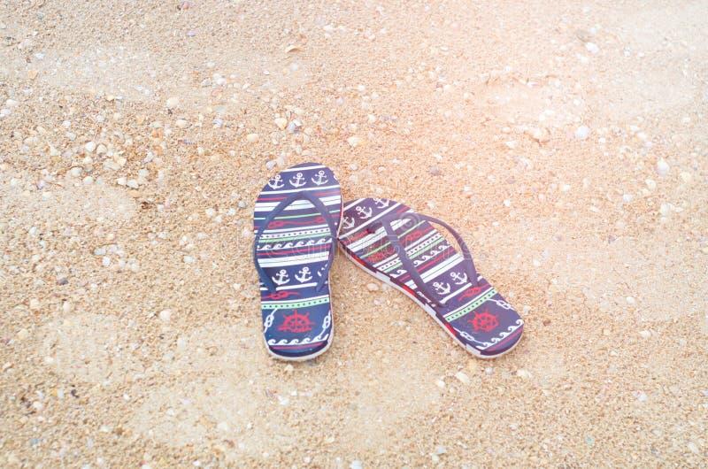 Pares de sandálias da praia na areia foto de stock