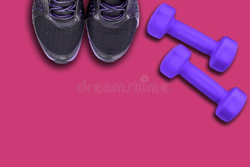 Pares de sapata, de sapatilha e de pesos pretos do ultravioleta da cor fundo cor-de-rosa/roxo fotografia de stock royalty free