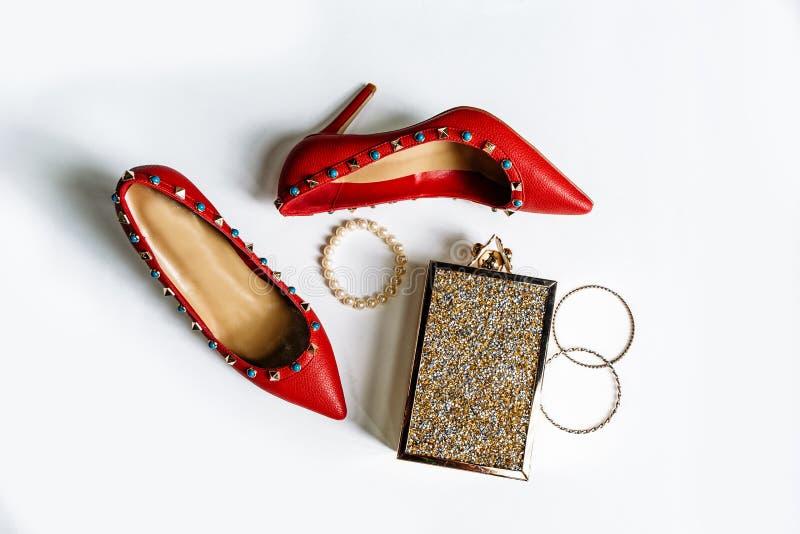 Pares de sapatas alto-colocadas saltos vermelhas com dedos do p? agu?ados, decorados com as inser??es do metal e a embreagem azui foto de stock