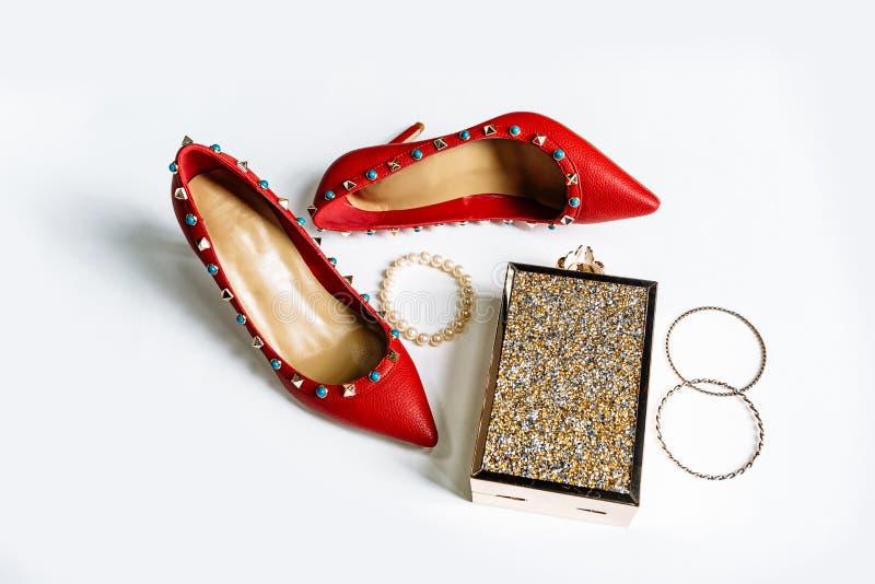 Pares de sapatas alto-colocadas saltos vermelhas com dedos do p? agu?ados, decorados com as inser??es do metal e a embreagem azui foto de stock royalty free