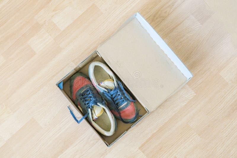 Pares de sapatas brandnew na caixa dos desenhos animados da sapata no assoalho de madeira f imagens de stock royalty free