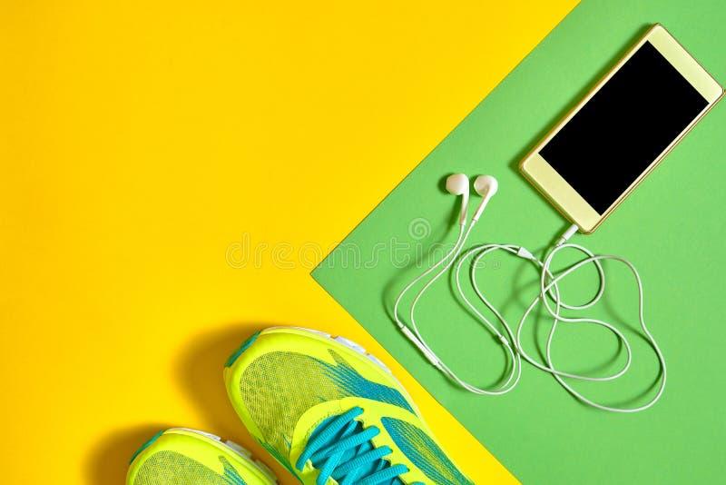 Pares de sapatas do esporte e de telefone celular móvel com os fones de ouvido no fundo colorido Sapatilhas novas no fundo verde  foto de stock