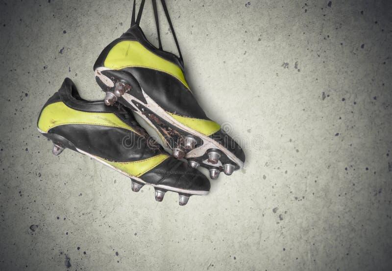 Pares de sapatas do futebol na parede imagens de stock