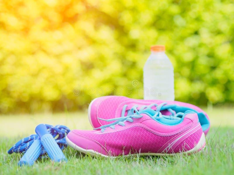 Pares de sapatas e de garrafa de água cor-de-rosa do esporte com grama verde imagem de stock royalty free