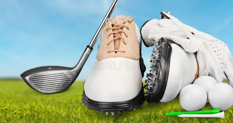Pares de sapatas golfing e de um clube de golfe no verde imagens de stock