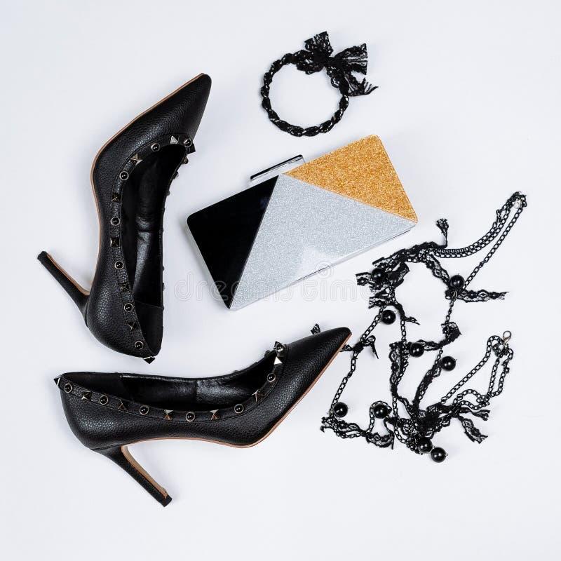 Pares de sapatas pretas decoradas com acentos do metal, joia com la?o e os gr?nulos pretos e uma embreagem tricolor com sparkles  imagens de stock royalty free