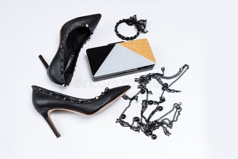 Pares de sapatas pretas decoradas com acentos do metal, joia com la?o e os gr?nulos pretos e uma embreagem tricolor com sparkles  fotos de stock royalty free