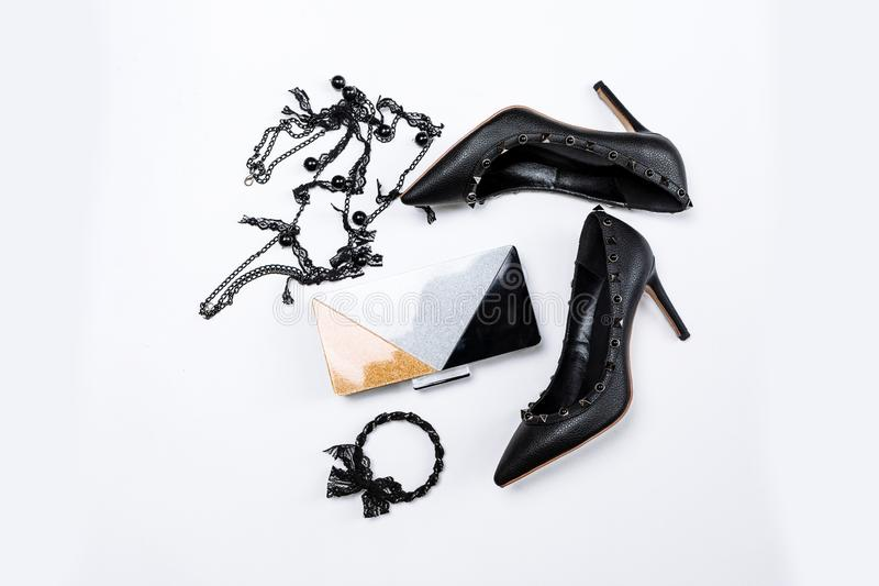Pares de sapatas pretas decoradas com acentos do metal, joia com la?o e os gr?nulos pretos e uma embreagem tricolor com sparkles  imagem de stock royalty free