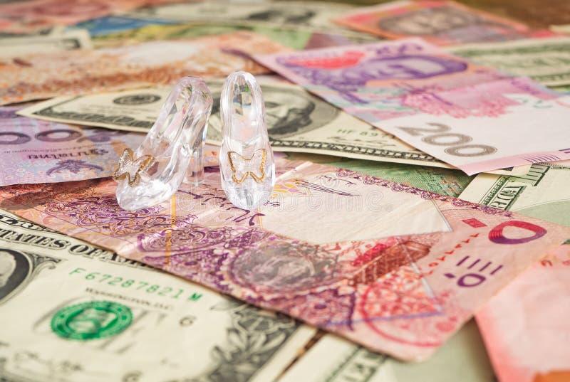 Pares de sapatas de vidro claros em moedas diferentes Dinheiro para o amor prostitui??o imagem de stock